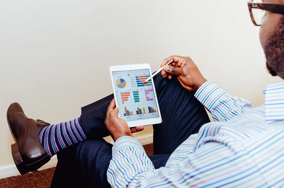 A man in business attire looking at stats and graphs on a white iPad