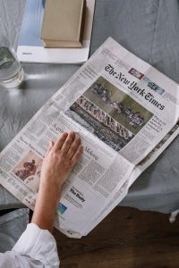 A person reading an open newspaper on a gray desk.